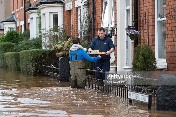 A man hands a tray of hot drinks and sausage sandwiches to residents remaining in their flooded properties in Carlisle northern England on December 7...