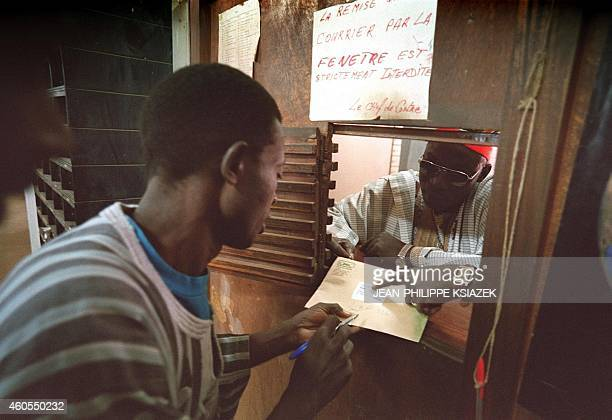 A man hands his letter to a postal workers in Ouagadougou 07 December 1999 The different services of Burkina Faso's post office dealing with some...