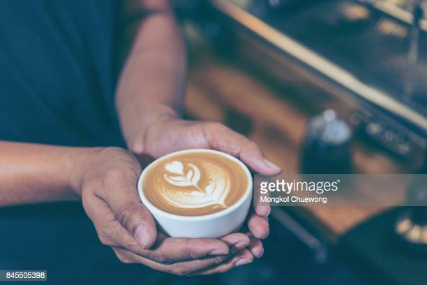 Man hands holding fresh coffee or latte art in white cup at coffee shop and restaurant, bar or pub.