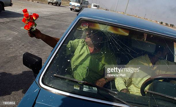 Man hands out flowers at a British check point April 6, 2003 on the outskirts of the Iraqi city of Basra, the strategic southern city that British...