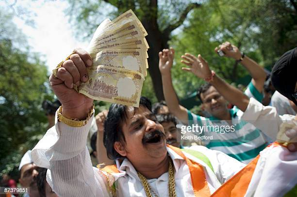 A man hands out money as supporters celebrate election results in front of the headquarters of the Congress Party on May 16 2009 in New Delhi India...