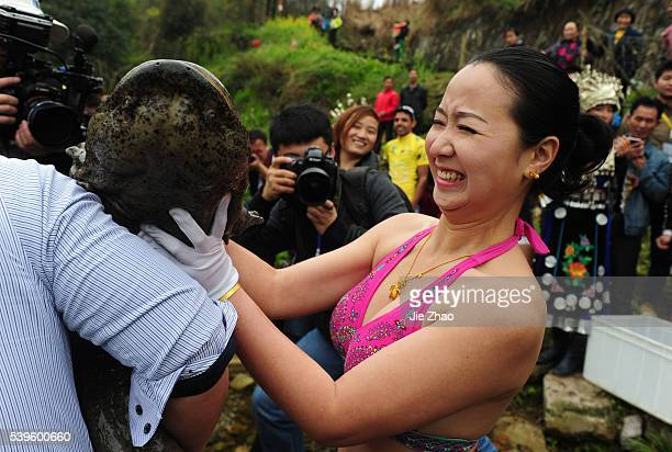 A man hands over a giant salamander to a woman in a freeing captive animals show to call everybody to protect environment in Zhangjiajie city Hunan...