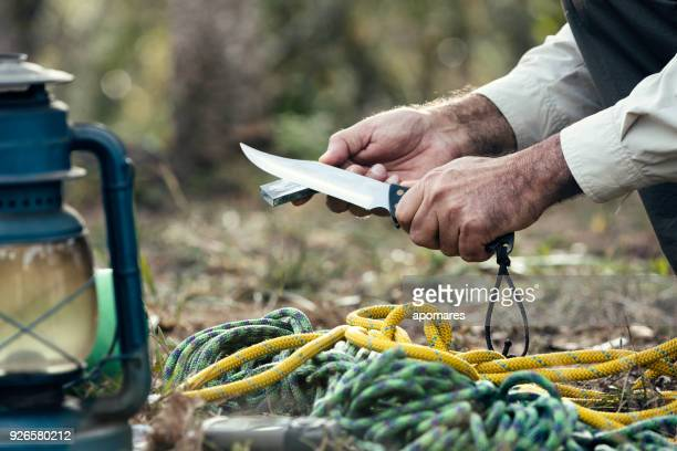man hands sharpening knife outdoors in the wilderness - territorio selvaggio foto e immagini stock
