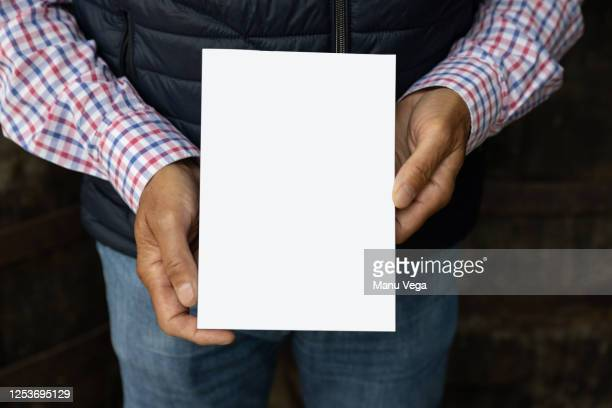 man hands show book, guy in plaid shirt, shows the white book, on camera - man holding book stock pictures, royalty-free photos & images
