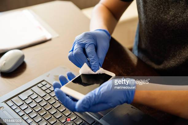 "man hands with gloves wiping mobile phone while working from home. - ""martine doucet"" or martinedoucet stock pictures, royalty-free photos & images"