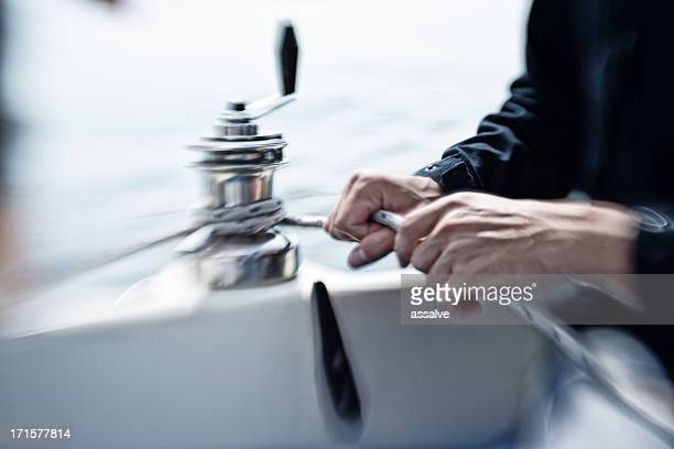 man hands working on a winch during sailturn - catamaran sailing stock photos and pictures