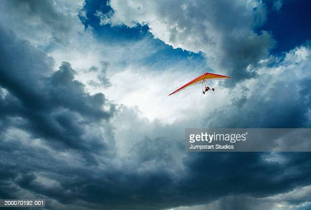 Man hanggliding through clouds in sky, low angle view