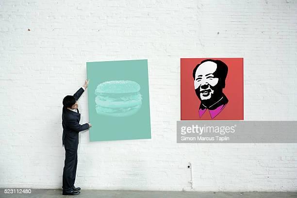 man hanging a painting - kunsthändler stock-fotos und bilder