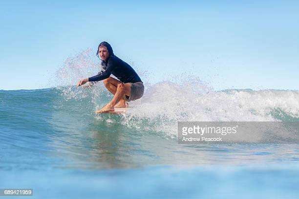 A man hanging five on a surfboard.