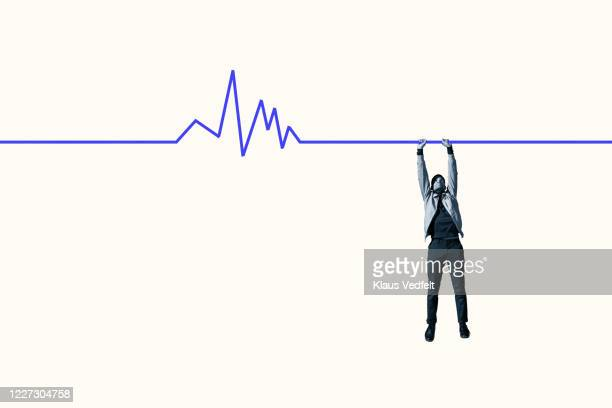 man hanging from blue line graph for survival - healthcare stock pictures, royalty-free photos & images