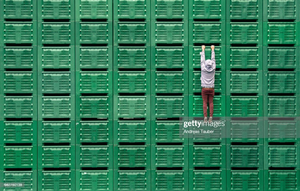 A man hanging from green servers. : Stock Photo