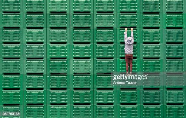 A man hanging from green servers.