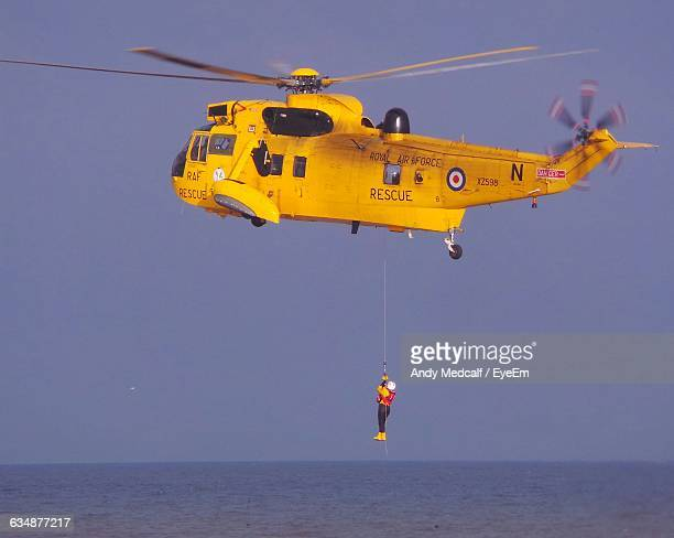 Man Hanging From Rescue Helicopter Flying Over Sea