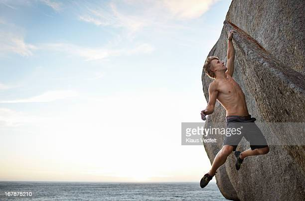 Man hanging in one arm on narrow rock over the sea