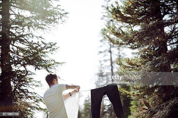 man hanging laundry in meadow - hängen stock-fotos und bilder
