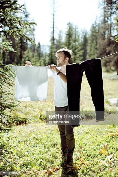 Man hanging laundry in meadow