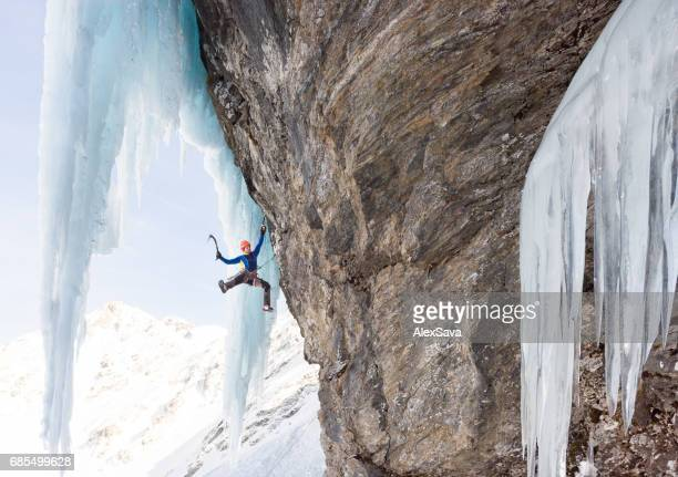 Man hanging on ice axe while climbing on frozen rock wall