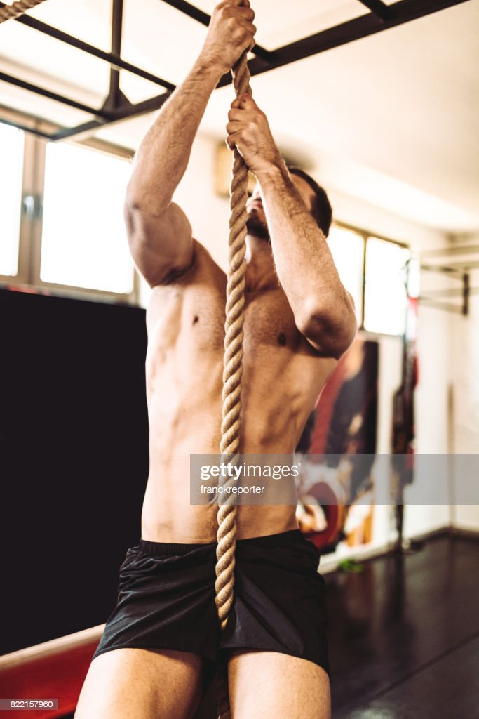 man hanging on the rope in the gym : Stock Photo