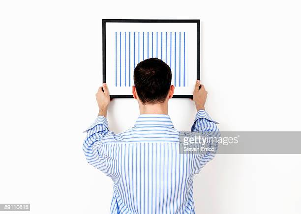 Man hanging picture frame on wall