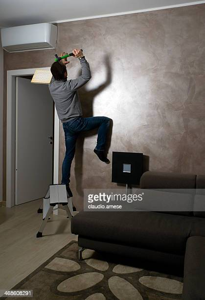 Man Hanging Picture Frames On Wall At Home. Color Image