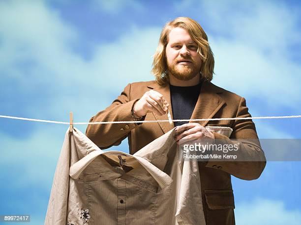 man hanging shirt on a clothesline