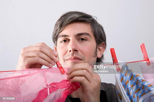 A man hanging underwear on a clothesline