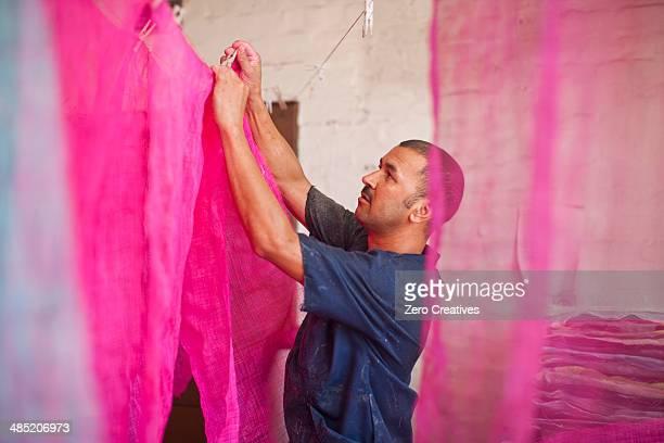 man hanging up dyed fabric in traditional milliners workshop - färbemittel stock-fotos und bilder