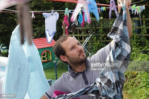 Man hanging washing in garden