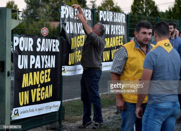 A man hangs a banner reading 'to save a farmer eat a vegan' as antispeciesist activists from the Association 269Life Liberation Animale organised an...
