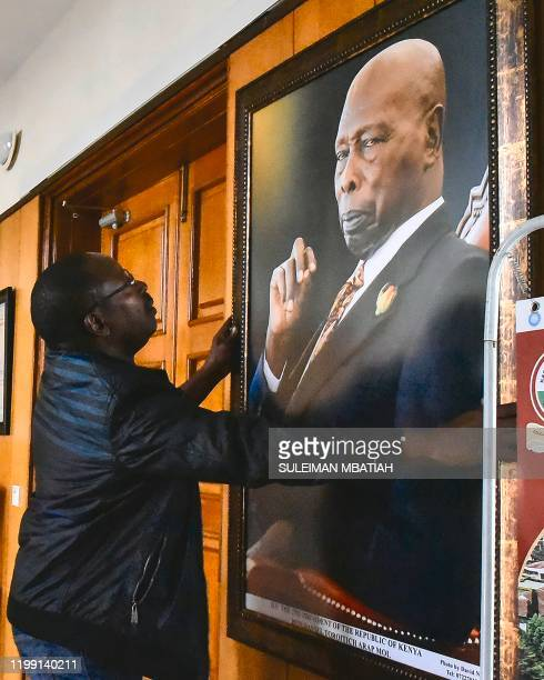 A man hangs a portrait on the wall of the late former President of Kenya Daniel arap Moi in Nakuru on February 7 2020 The state funeral for Daniel...