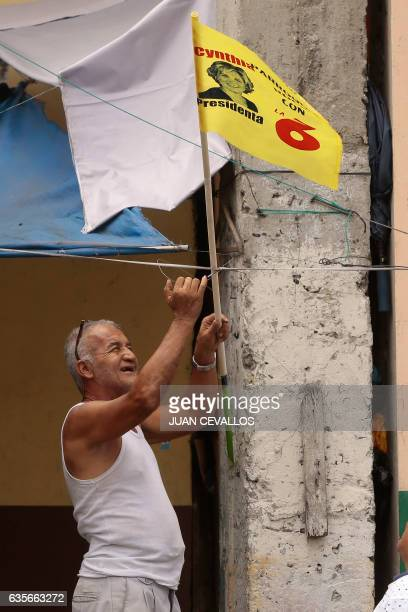 A man hangs a propaganda flag of Ecuadorean presidential candidate for the Social Christian party Cynthia Viteri in Guayaquil Ecuador on February 16...