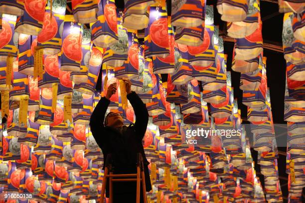 A man hangs a wish ribbon at a lantern show on February 8 2018 in Xi an China Chinese People are preparing for the upcoming Chinese Lunar New Year...