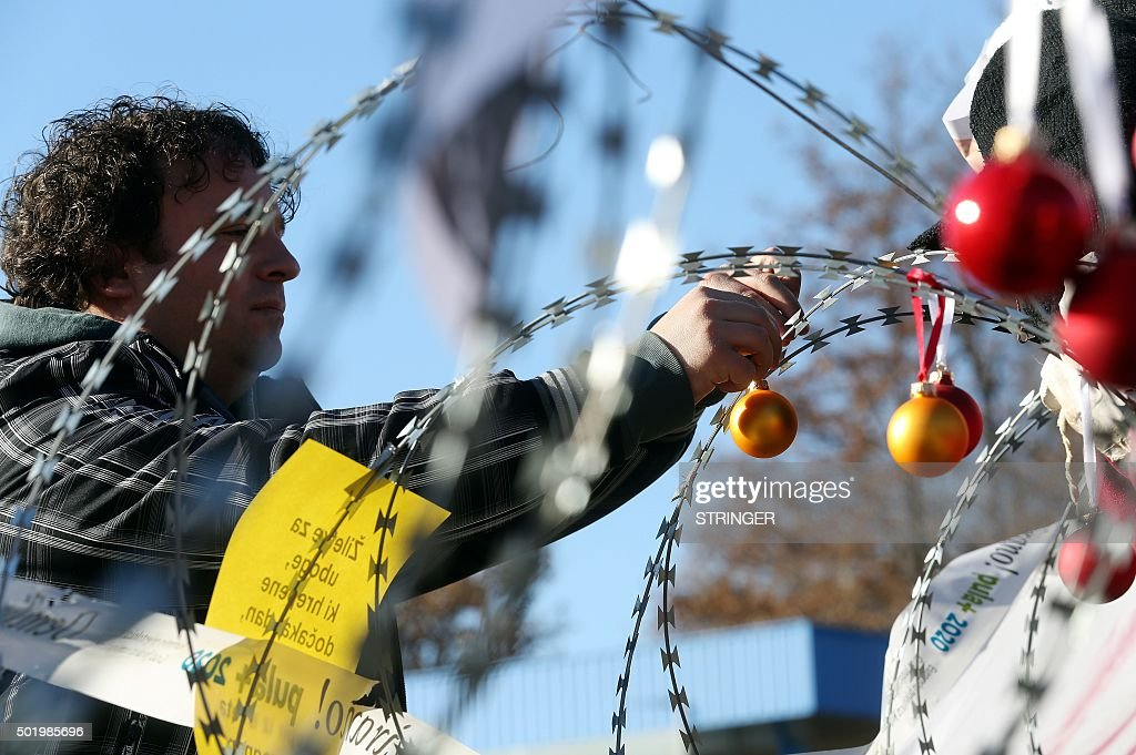 A man hangs Christmas ornaments on a razor-wire fence on the Lucija Brezovica border crossing on December 19, 2015 during a demonstration by Croatian and Slovenian protesters against the fence rolled out by Slovenia on Croatia's border to block the path of migrants. / AFP / STRINGER