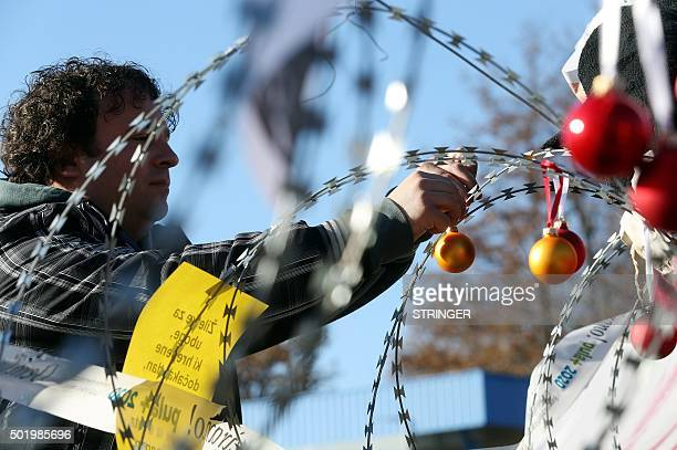 A man hangs Christmas ornaments on a razorwire fence on the Lucija Brezovica border crossing on December 19 2015 during a demonstration by Croatian...
