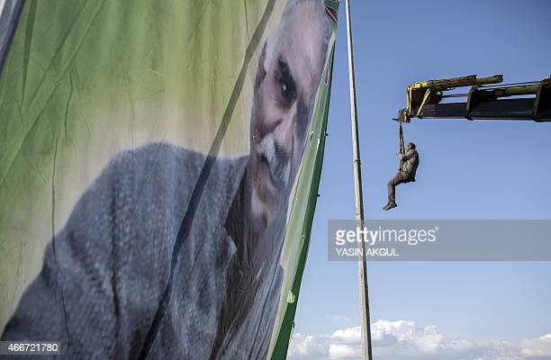 A man hangs from a crane while hanging a huge portrait of jailed Kurdish leader Abdullah Ocalan as people gather for celebrations surrounding Newroz...