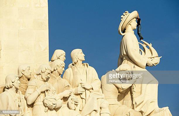 A man hangs from the hat of Prince Henry Duke of Viseu at the Monument of the Discoveries at Belem Lisbon The man has found a way to scale part of...