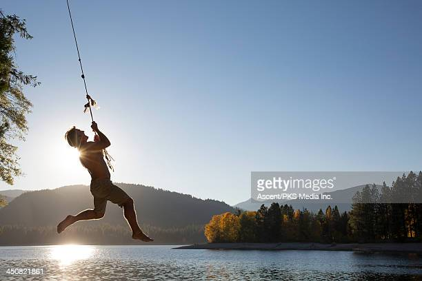 Man hangs onto rope swing above lake, hills