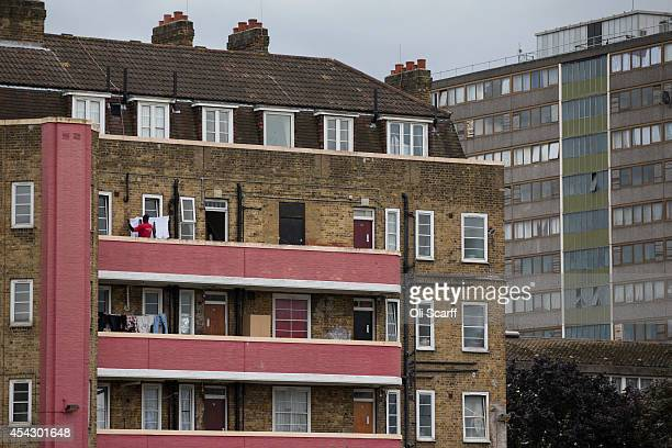 A man hangs out washing on a residential tower block in an area of Southwark with a high concentration of social housing on August 28 2014 in London...