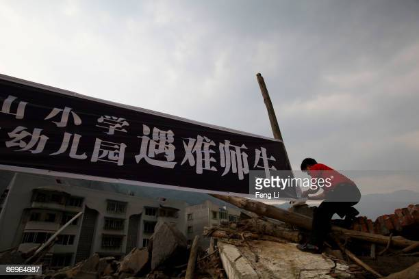 A man hangs the banner which mourns for teachers and students died in Sichuan Earthquake at the ruins of earthquakehit Beichuan county on May 11 2009...