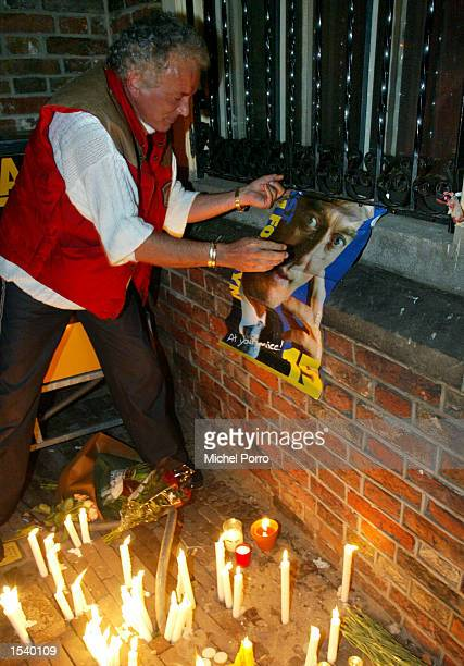 A man hangs up a poster on the parliament building for slain controversial Dutch rightwing politician Pim Fortuyn May 6 2002 in The Hague Netherlands...