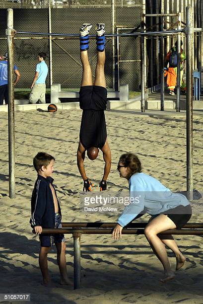 Man hangs upside-down at Muscle Beach, the birthplace of the sport of bodybuilding in the 1930s and 1940s, July 12, 2004 in Venice, California. An...