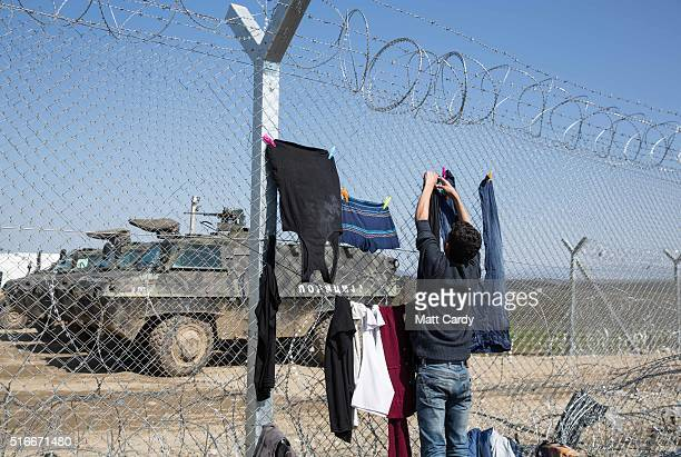 A man hangs washing to dry on the border fence at the Idomeni refugee camp on the Greek Macedonia border on March 20 2016 in Idomeni Greece Thousands...