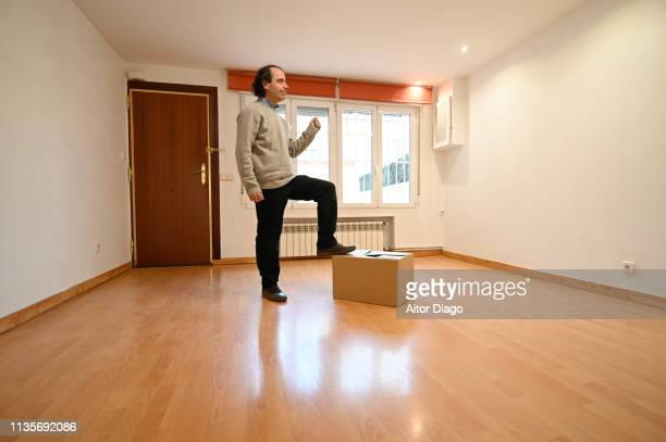 man happy with his foot on a cardboard box. he is moving - oggetti pesanti foto e immagini stock