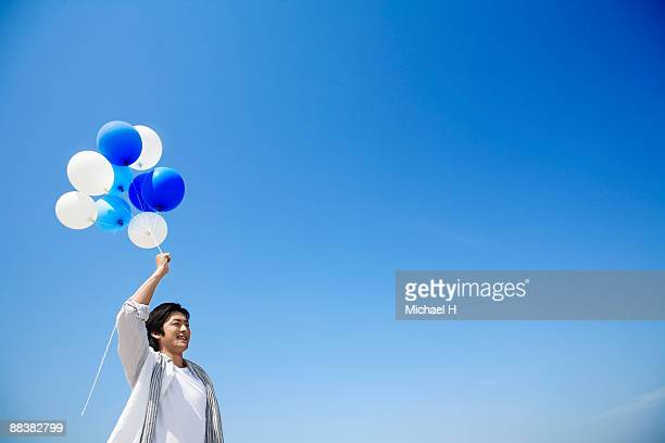 A man has a blue balloon.