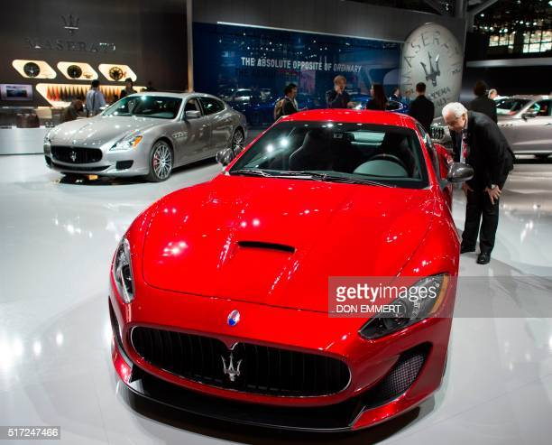 A man has a close look at a Mazerati GranTurismo MC March 24 at the New York International Auto Show / AFP / Don EMMERT