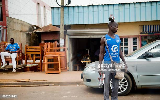 A man has a shoe on his head for sale in Yaounde on March 16 2015 in Yaounde Cameroons on March 16 2015 in Yaounde Cameroon