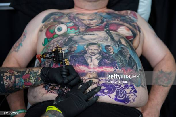A man has a tattoo applied to his torso during the Great British Tattoo Show at Alexandra Palace on May 27 2018 in London England The show hosts over...