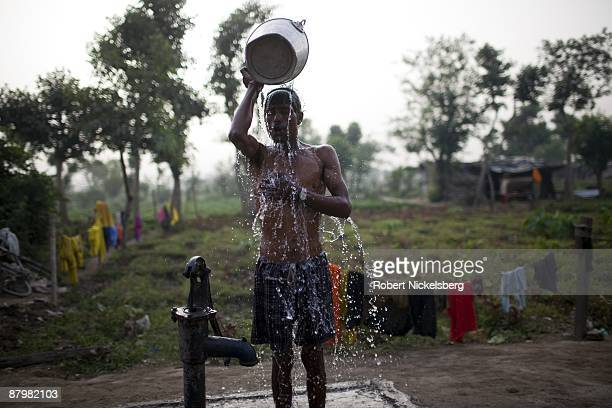A man has an open air bath in a slum area near a newly dug roadway April 21 2009 where agricultural areas he and members of twelve families have been...