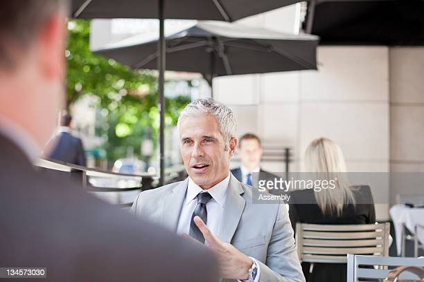 Man has business discussion on restaurant patio.