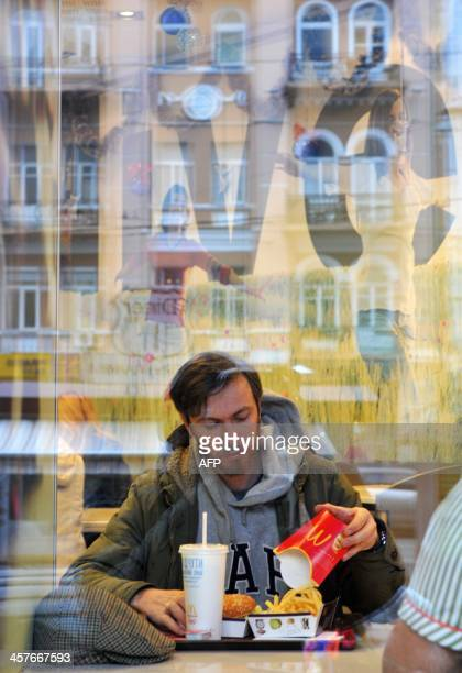 A man has dinner in a fast food restaurant in the centre of Kiev on December 18 2013 AFP PHOTO/ YURIY DYACHYSHYN